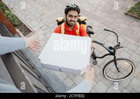 Online order and pizza at home. Smiling courier in helmet, gives boxes to client, near house Stock Photo