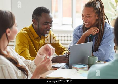 Portrait of African-American man and woman laughing cheerfully while working on team project with multi-ethnic group of people, copy space
