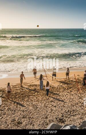 A group of holidaymakers playing a game of volleyball on Fistral Beach in Newquay in Cornwall. - Stock Photo