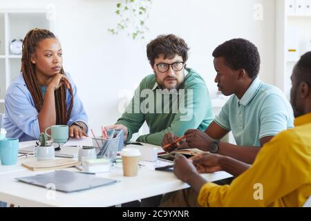 Portrait of bearded mature manager talking to multi-ethnic business team while discussing plans during meeting in office, copy space Stock Photo
