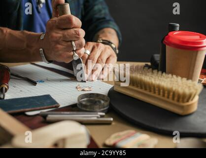 Handmade leather artisan making craft wallet using piece of natural leather on his working place with coffee and polishing brush , close up photo of h - Stock Photo