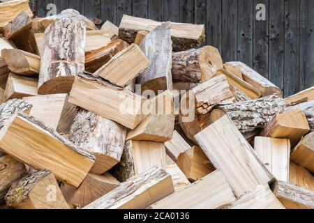 Dry chopped firewood background. Preparation of firewood for winter. Rural cozy firewood backdrop. Natural, organic concept
