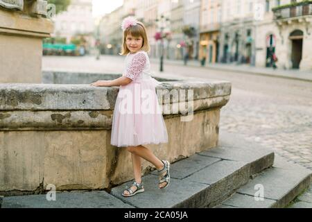 Adorable little blond girl in beautiful pink dress posing to camera at old fountain of ancient European city outdoors. Full length portrait of happy - Stock Photo