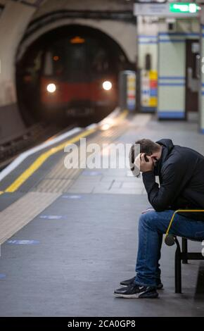 Young man sits with head in hands on a London Underground platform station, with train approaching. London, England UK - Stock Photo