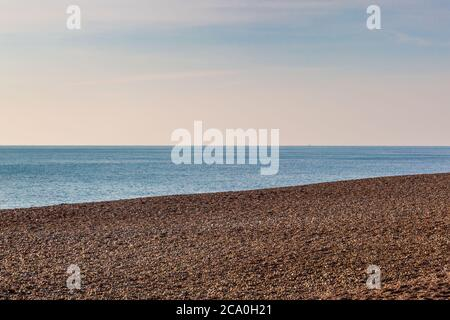 Looking out to sea over the pebble beach at Hove, on a sunny winters day - Stock Photo