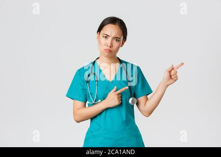 Covid-19, healthcare workers, pandemic concept. Disappointed and angry asian female therapist, nurse in scrubs looking upset at camera, sulking and