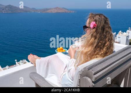 Beautiful young woman with flower in hair coffee cup sitting on white terrace balcony of house or hotel with Sea View
