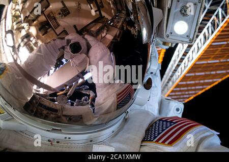 NASA astronaut Bob Behnken conducts a six-hour spacewalk with fellow astronaut Chris Cassidy outside the International Space Station June 26, 2020 in Earth Orbit. - Stock Photo