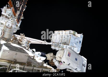 NASA astronaut Bob Behnken conducts a six-hour spacewalk with fellow astronaut Chris Cassidy to swap an aging nickel-hydrogen battery for a new lithium-ion battery outside the International Space Station July 1, 2020 in Earth Orbit. - Stock Photo