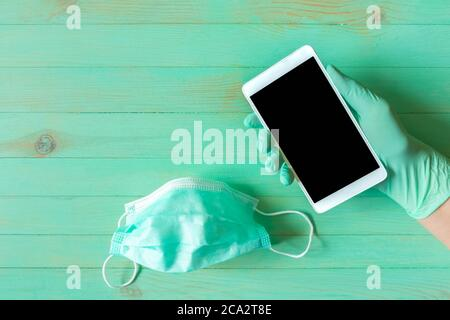 Hand in disposable glove holding mobile phone and medical mask on wood background. Hand in glove with smartphone and protective facemask on table. Com Stock Photo