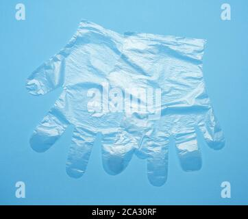 pair of disposable polyethylene gloves on a blue background, top view, flat lay.