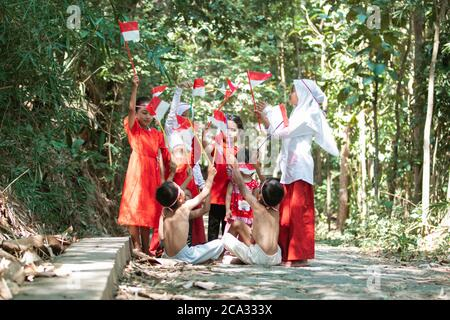 group of children holding small red and white flag and raised together on lots of trees in the background
