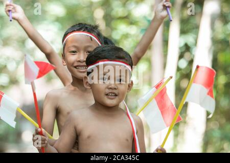 close up of children face when holding small red and white flag and raised together the flag on with lots of trees in the background
