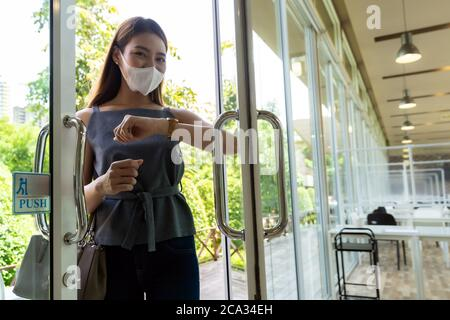 Portrait of asian attractive woman using elbow to push restaurant door open to reduce hand touching on public place to reduce chance to infection by