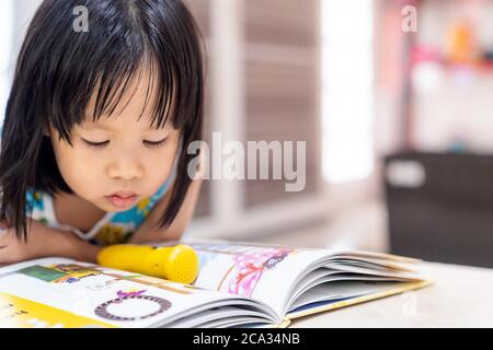 Asian girl child reading interactive book in living room at home as home schooling while city lockdown because of covid-19 pandemic across the world. - Stock Photo