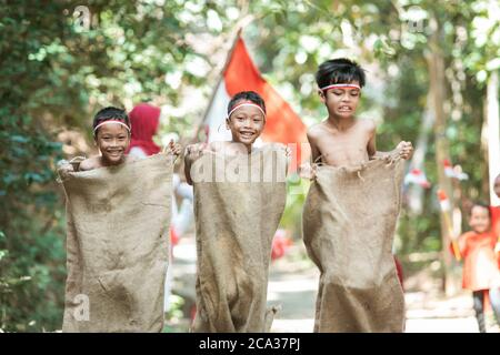 three children try to run fast and jump in the sack race with friends support them on Indonesian independence day