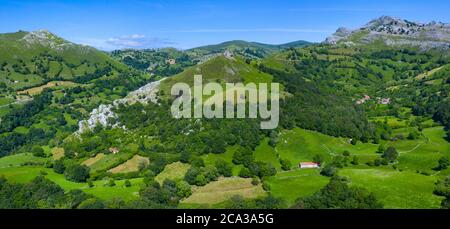 Spring landscape of mountains, meadows of mowing and cabins pasiegas in the Miera Valley, Cantabria, Spain, Europe. - Stock Photo