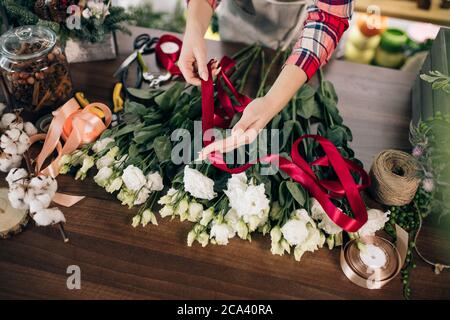 cropped careful florist making, composing bouquet of white beautiful roses for customer in her own shop, red ribbon on flowers. plants, flowers, decor