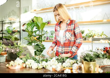 young caucasian florist at work, pretty young blond female making fashion modern bouquet of different flowers wearing red casual shirt - Stock Photo