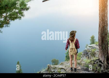young hiker girl looking at the distance while having a rest on the top of hill, full length photo. copy space. blue river, lake in the background of Stock Photo