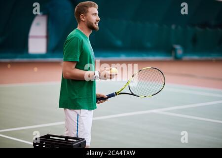 Young bearded man in green sportwear is playing tennis on indoor court, holding ball in hand. - Stock Photo