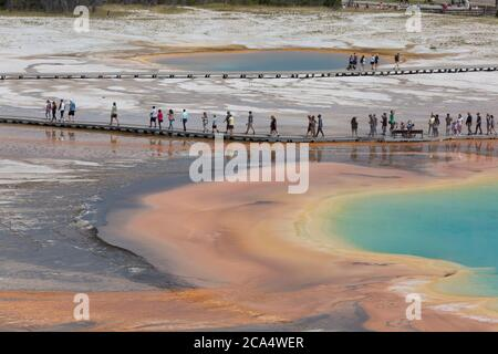 Visitors walk along the boardwalk at Grand Prismatic Spring on Monday, August 3, 2020. Many of the parks boardwalks have been made one-way in order to combat the transmission of the COVID-19 virus. The park recently reported several positive cases of the COVID-19 virus among visitors and concessioners. - Stock Photo