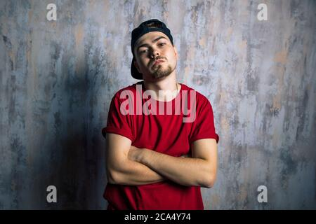 handsome man in fashion clothes posing to the camera. hip hop lovers, street art concept. - Stock Photo
