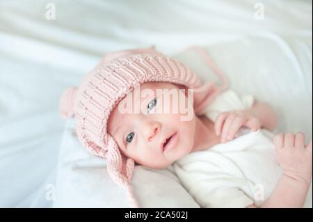 Newborn baby lying on bed with hat