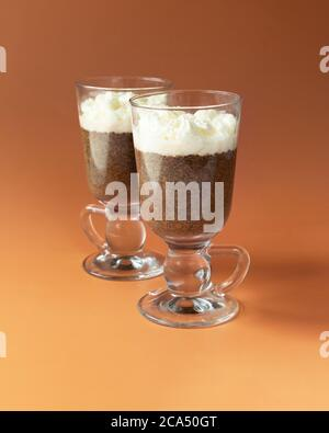 Coffee Chia pudding in glass on brown - orange color background. - Stock Photo
