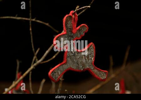 Wooden christmas ornament shaped as reindeer hanging on a dry tree branch - Stock Photo