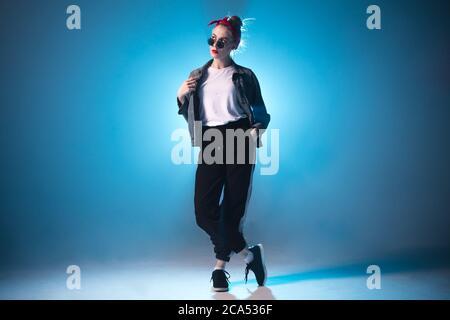 Stylish woman dancing solo on hip hop party. Sunglasses, modern black dance wear, neon lights. - Stock Photo