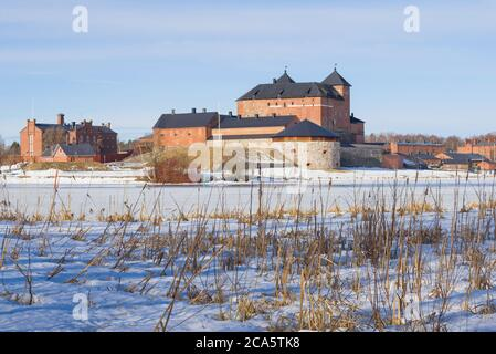 View of the ancient fortress of the city of Hameenlinna from the shore of Vanajavesi lake on a sunny March day. Finland - Stock Photo