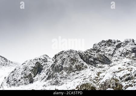 Rock formation with settled snow and snow flakes after storm Ciara. Near 'Devils Kitchen' in Wales. - Stock Photo