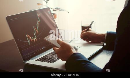 investment stockbroker predicting bitcoin price trend movement using laptop and phone - Stock Photo