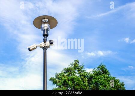 Two white surveillance cameras on the metal lamp post in public park.  - Stock Photo
