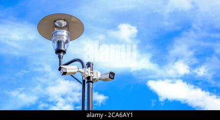 Two white surveillance cameras on the metal street light lamp post outdoor  - Stock Photo