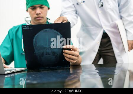 Doctors looking at x-ray film of patient 's head - Stock Photo