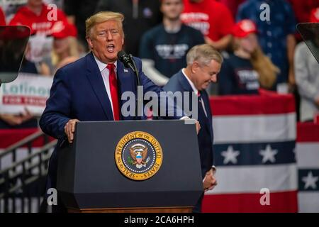 Senator Lindsey Graham waits behind President Trump at the rally in the Bojangle's Coliseum Stock Photo