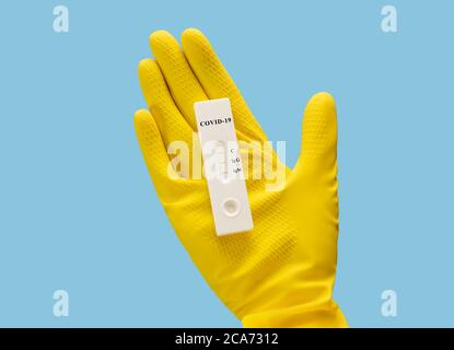 New coronavirus test in hand on a blue background. Unused covid-19 test cassette. Hand in a yellow glove with a test. Close up. - Stock Photo