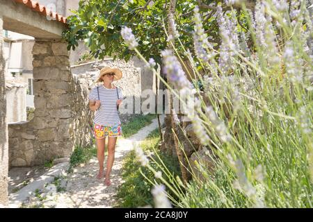 Rear view of beautiful blonde young female traveler wearing straw sun hat sightseeing and enjoying summer vacation in an old traditional costal town - Stock Photo