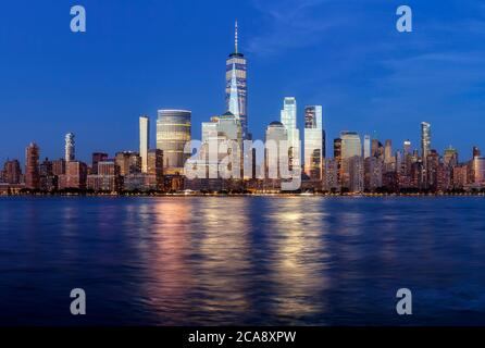 Manhattan skyline at dusk with city lights reflected in water, New York City, USA.