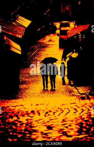 Silhouette of two women under one umbrella walking down a cobblestone alley in Stockholm