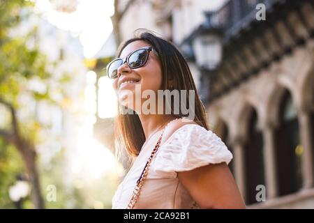 woman with sunglasses smiles as she walks through town