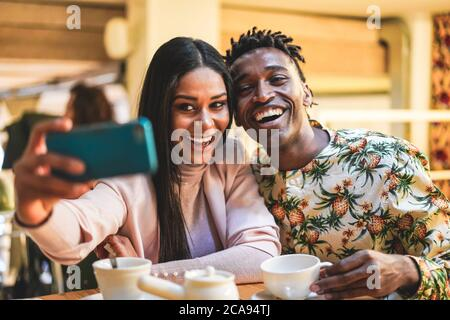 Happy black couple drinking coffee inside bakery while taking selfie with mobile phone - Young people having fun with technology trends - Social media