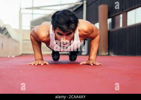 handsome sportsman doing push ups on a red floor, concept of urban sport and healthy lifestyle, copy space for text - Stock Photo