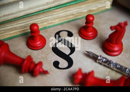 Closeup of isolated paragraph symbol on old yellow vintage paper with books, ink pen and red chess pieces (focus on paragraph symbol) - Stock Photo