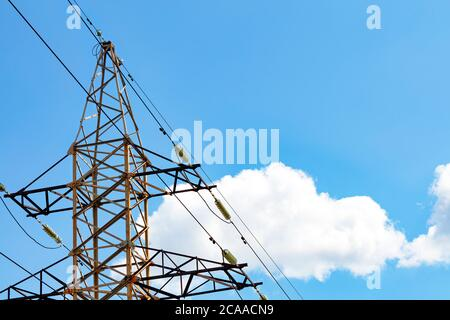 A metal power line support with insulators and wires used to support an overhead power line against white cloud and blue sky background, copy space. - Stock Photo