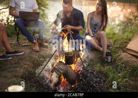 Cooking in a pot on campfire. closeup photo of a great bonfire at campsite. - Stock Photo