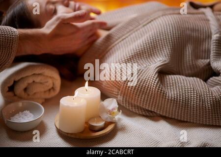 Young girl having massage on her face in spa salon. Wearing bathrobe, candles near her. Beauty treatment