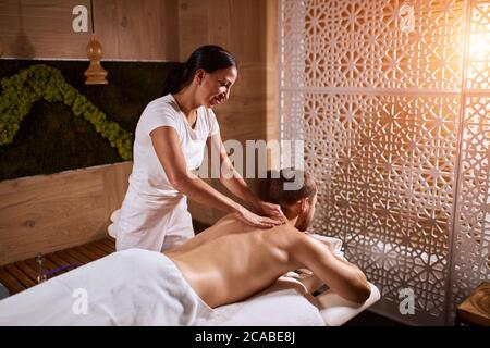 Charming pleasant woman wearing white uniform, working in spa hotel, massaging back of male client in brightly lighted room of hotel, total relaxation